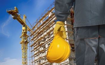 worker with helmet in front of construction scaffolding and crane