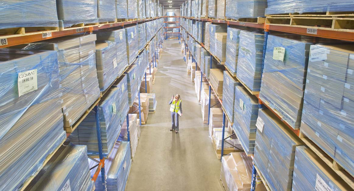 warehouse worker inspects warehouse pallets
