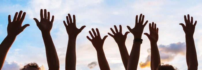 image of hands raised to sky