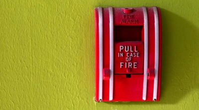 fire alarm switch on green painted wall