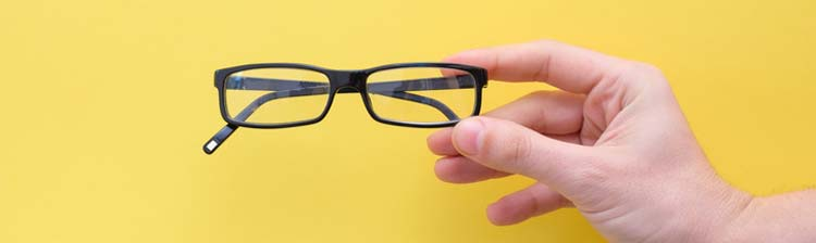 spectacles held in front of yellow background