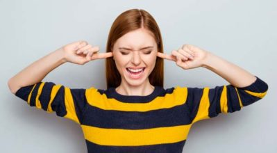 woman blocking out noise with fingers in ears