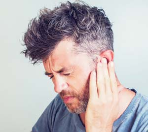 man suffering from tinnitus