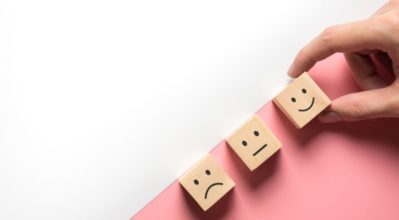 Three wooden blocks showing happy, neutral and sad faces.