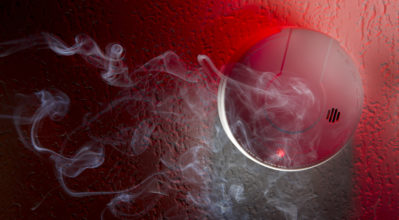 Smoke detector mounted on ceiling with white smoke, red warning light