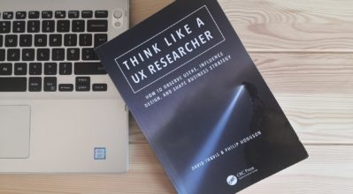 The book 'Think Like a UX Researcher' on a desk