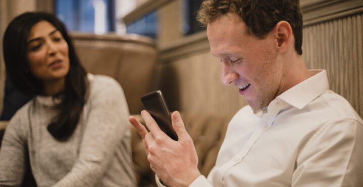 A man with his smartphone in his hand and he is using a visually impaired mobile app to help assist him, a female can be seen sitting down next to him.