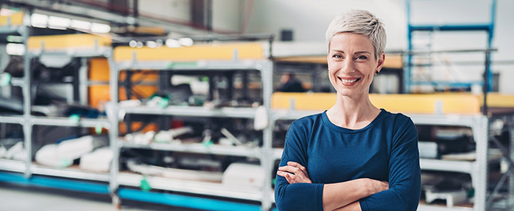 Portrait of a smiling woman standing by industrial racks