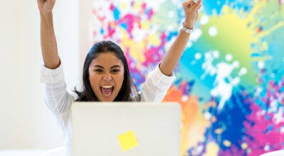 A girl celebrating in a colourful office environment.