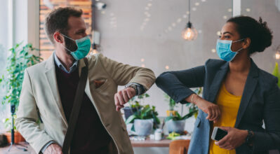 Two colleagues wearing face masks touching elbows (instead of shaking hands)