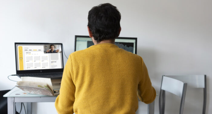 Man sitting at a table/desk using a computer