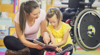 A little girl sitting and reading with her caregiver at school.