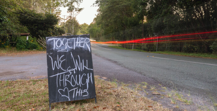"""Roadside chalk board, with the words """"Together we will get through this"""""""