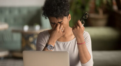 A female sitting at a laptop, holding glasses and pinching the bridge of her nose. representing eye strain / fatigue