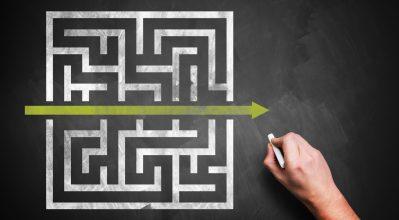 "(alt=""A hand drawing a shortcut through a maze on a chalkboard"")"