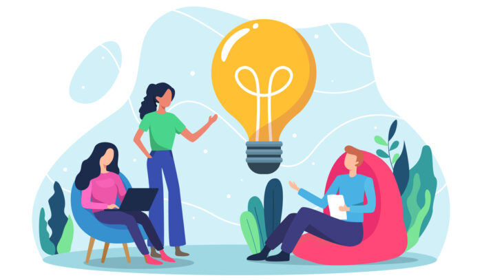 """(alt=""""Vector image of 3 people talking, one with a laptop, one with notes, the other standing. With a light bulb in the middle to suggest talking about ideas"""")"""