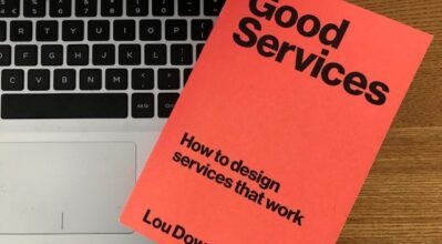 """(alt=""""the cover of the book, good services by Lou Downe on a laptop"""")"""